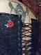 Corset sur la poitrine en tissu noir aux reflets violets, brodé de roses rouges