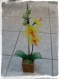 Une orchidée en nylon jaune et orange dans un pot