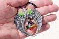 Pendentif en ailes d'ange formant un coeur avec au centre une grappe de perles multicolores en cristal