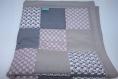 Couverture bébé en patchwork motifs géométriques, tons de gris.