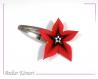 Barrette fleur star rouge et noire à perles blanches et orange transparentes.