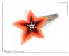 Barrette fleur star orange et centre Étoile noire à perles blanches et dorées transparentes.