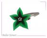 Barrette fleur star vert foncé et centre grande Étoile noire à perles blanches et oranges.