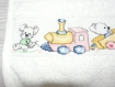 Bavoir bébé broderie points de croix lapins dans le train cadeau naissance