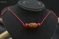 Collier - dragon ciselé dans un noyau de canarium et perle de corail