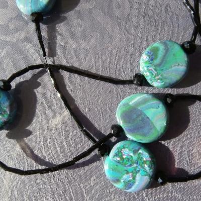 Collier sautoir perles plates, perles noires et rocailles.
