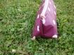 Trousse triangulaire violette à pois blancs.