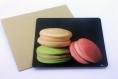 Carte postale «macarons » illustrée de 3 macarons beige, rose et vert sur fond noir