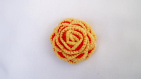 Fleur jaune et orange, montée en broche, au crochet