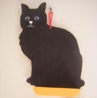 Tableau noir en forme de chat , avec craie et éponge .