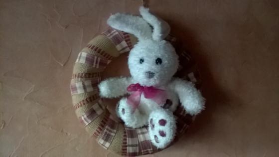 Lapin  blanc en peluche lové dans cercle paille recouvert de toile de jute naturelle et rouge et de ruban écossais
